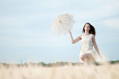 Sad woman with umbrella runing in field