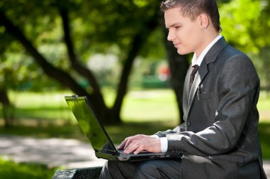 Business man work on notebook at park. Student