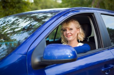 Blonde woman sitting behind the wheel of a car
