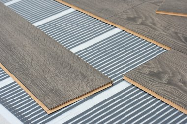 Infrared floor heating system under laminate floor