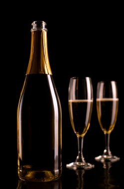 Champagne glasses and bottle on black background. New Year celeb