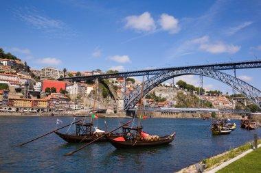 Tradicional vintage port transporting boats near famous bridge P