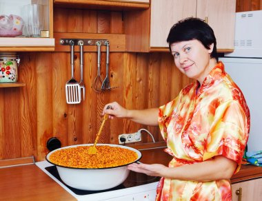 Woman cooks a jam of sea-buckthorn