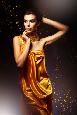 Woman in long yellow dress and jewelry