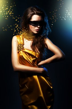 Woman in long yellow dress and jewelry blindfolded