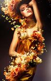 Smyslná žena v dlouhých žlutých šatech a květiny