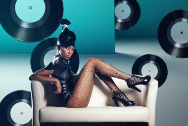 Attractive african woman siting in white chair on vinyl records