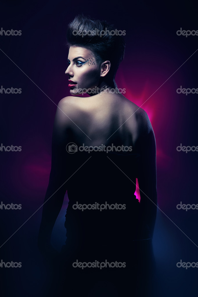 Brunette woman with red lips in dark magenta light