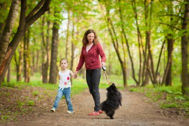 Mother and child walking playing with dog