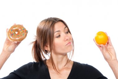 Woman comparing unhealthy donut and organic orange