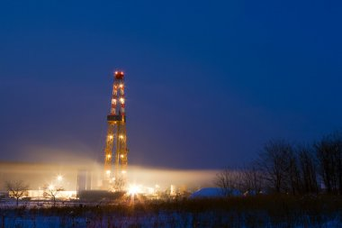 Oil well in the field illuminated at night.