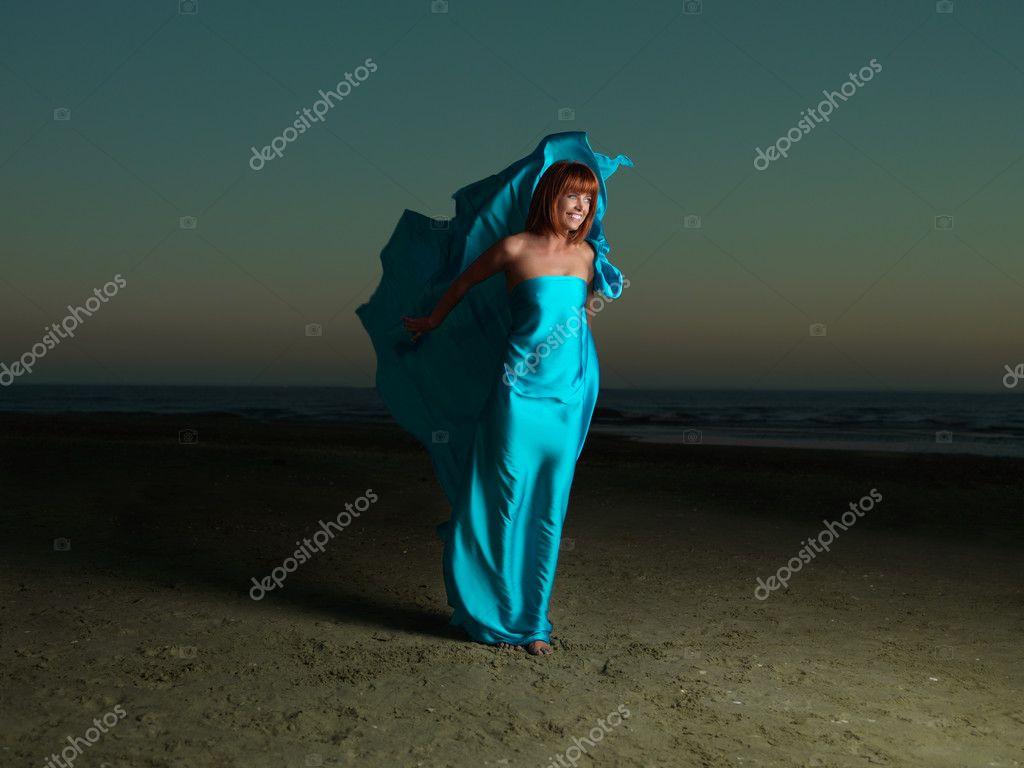 Happy woman desert beach wind blowing dress