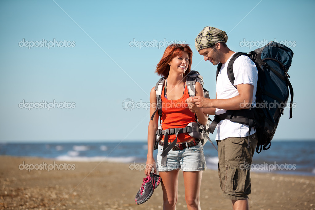Couple with backpacks walking on sea shore