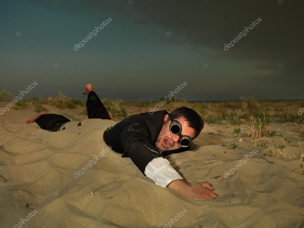 Young businessman swimming through sand in suit