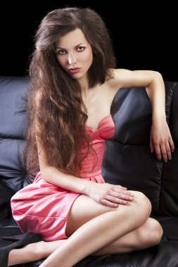 Brunette in pink on sofa, she has the elbow on the sofa's back