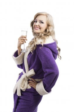 Blond haooy girl in bathrobe drinking champagne, she looks up an