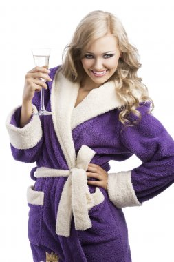 Blond haooy girl in bathrobe drinking champagne, she is on front