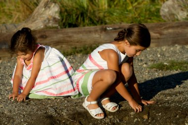 Sisters crouch to play with sand & rocks.