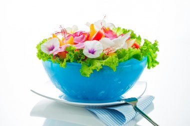 Fruit salad with edible flowers in a blue bowl from ice on white