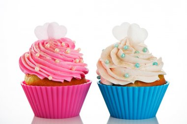 Two cupcakes in a pink and blue baking cups with pink and white