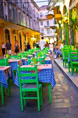 Typical greek taverna with tables outside on the street of Mediterranean Corfu town , street night scene