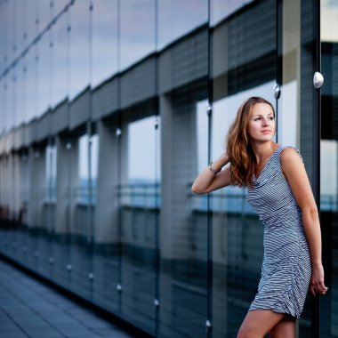 Young woman posing inside a modern top architecture building