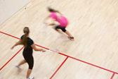 dva ženské squashové hráče v rychlých akcí na squashovém kurtu