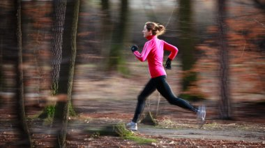 Young woman running outdoors in a city park on a cold fall