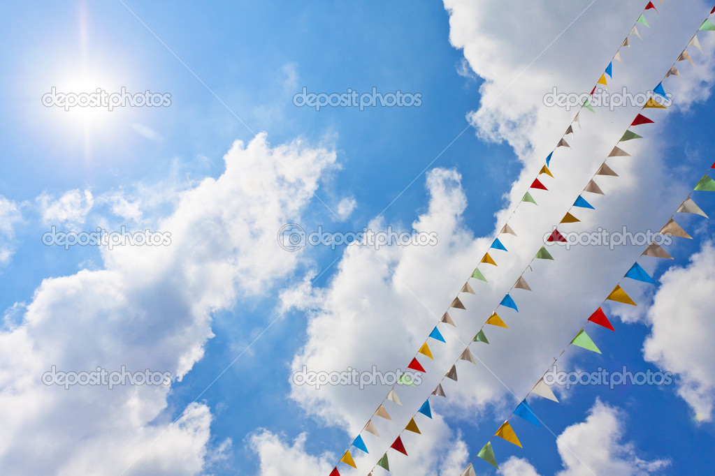 Blue sky with multi colored party flags hanging