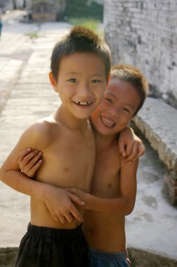 Two young Chinese boys smiling in a village