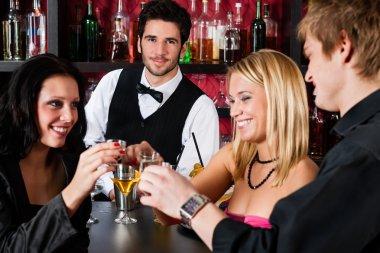 Barman behind counter friends drinking at bar