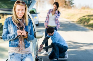 Puncture wheel man helping two female friends