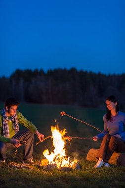 Couple cook by bonfire romantic night countryside