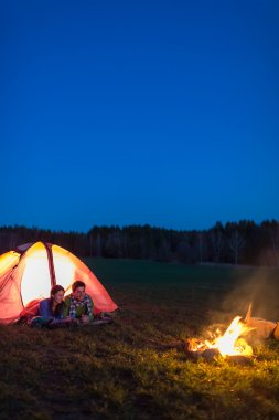 Camping night couple lying front tent campfire