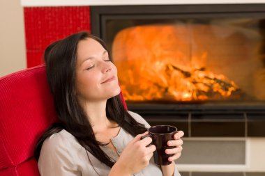Winter home fireplace woman drink closed eyes