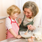 Fotografie Child girl and grandmother baking cake