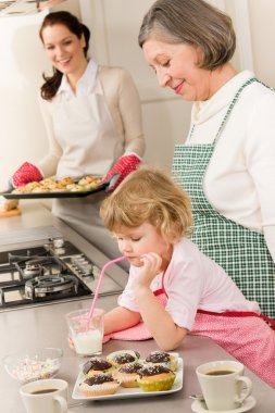 Three generations of women baking in kitchen