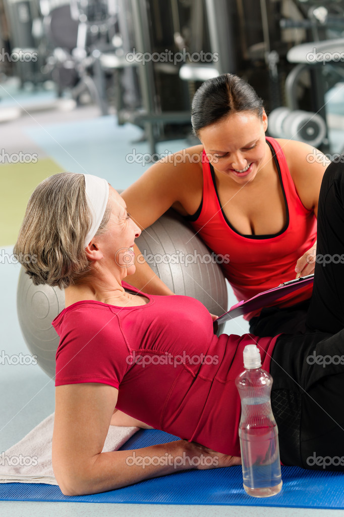 Fitness center senior woman relax on mat with personal trainer