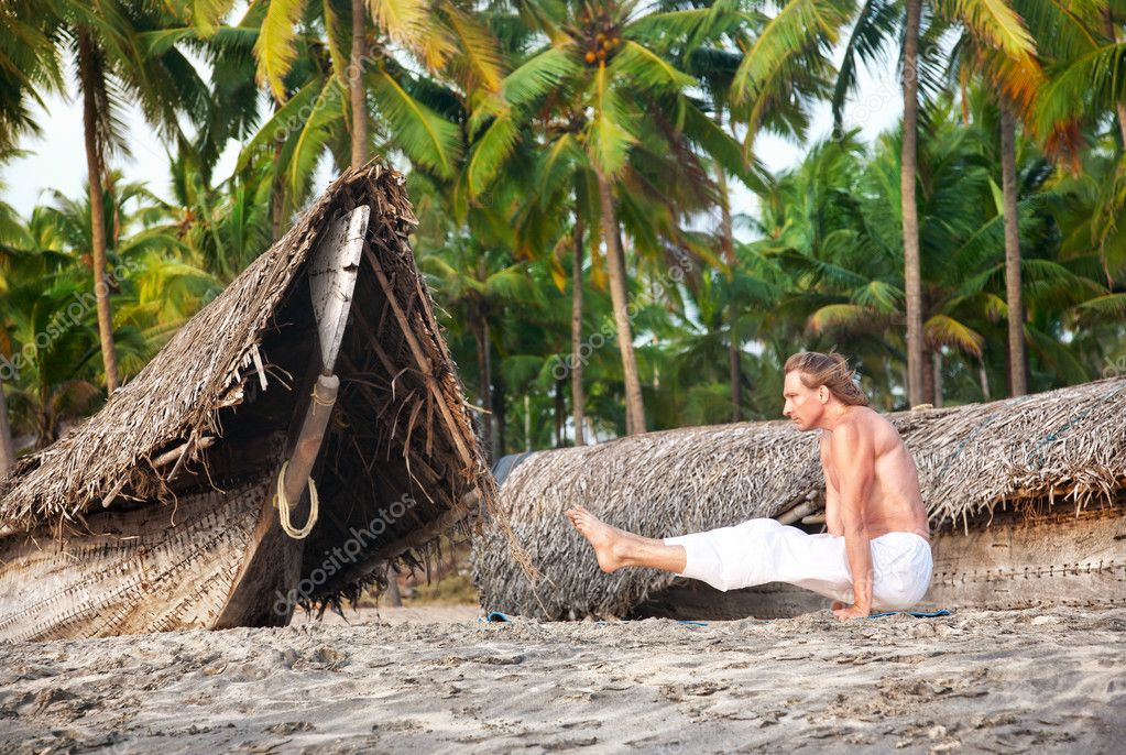 Yoga angusthasana pose on the beach