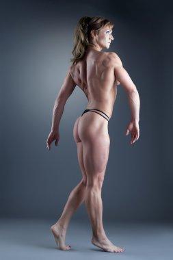 Strong woman body builder walk side
