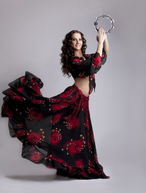 Young woman dance flamenco with tambourine