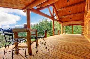 Porch of the log cabin with small table and forest view.