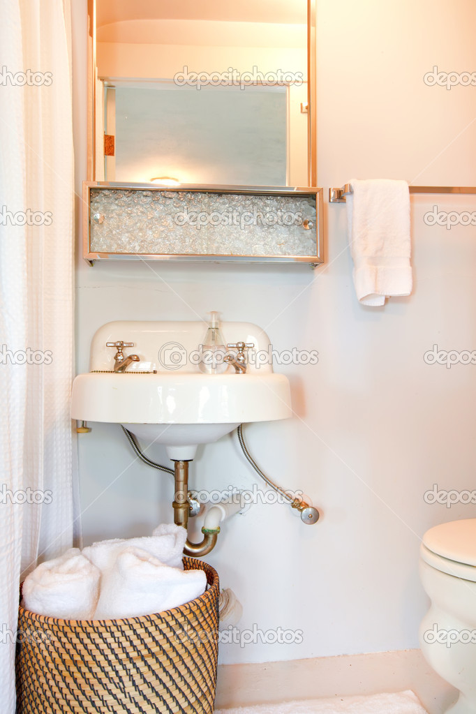 petite salle de bain bleu avec évier antique et serviettes blanches ...