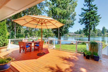 Large deck with umbrella and view of the lake
