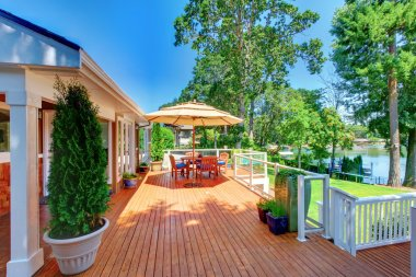 Large orange deck with umbrella and house and railing.