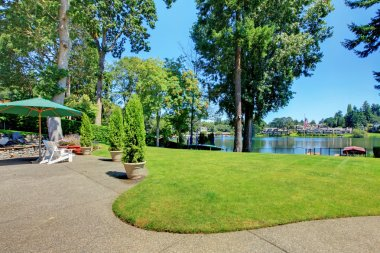 Large back yard with the view of the lake and outdoor area.
