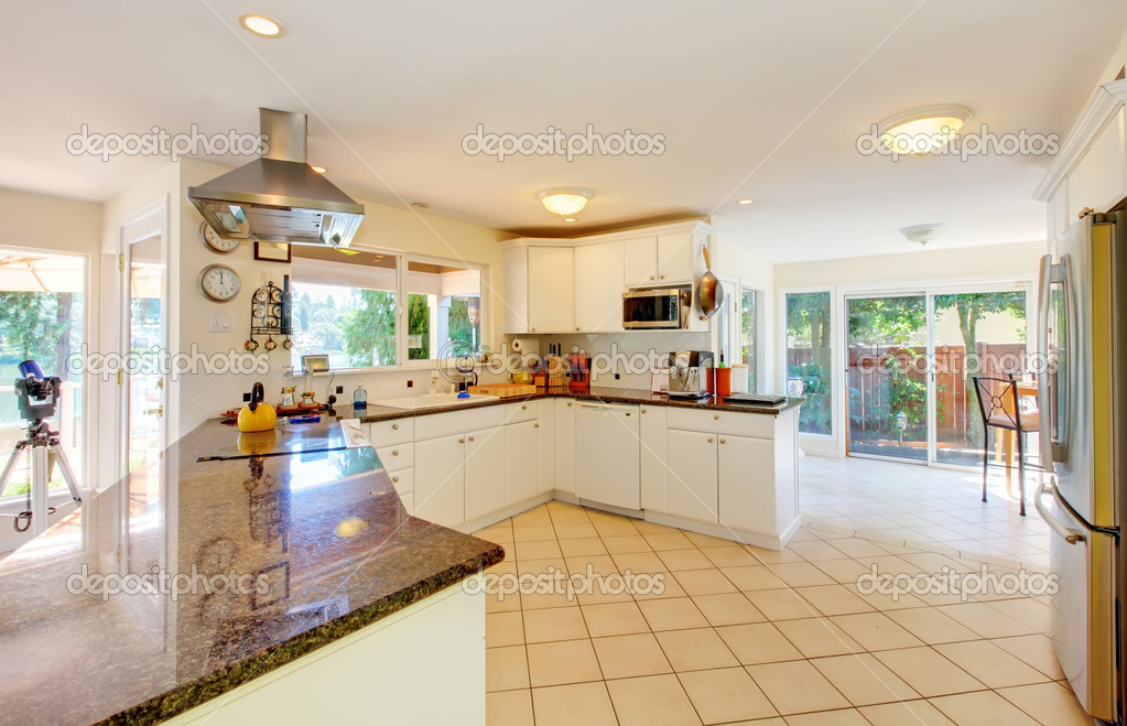 grande cuisine beige et blanche avec une chambre lumineuse à l ...
