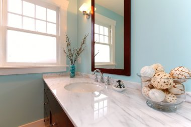 Blue bathroom with white marble sink.