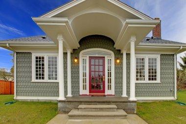Front shot of cute grey house with pink door.
