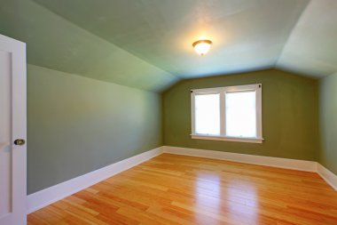 Attic green room with low ceiling and hardwood floor.
